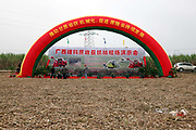 Red banners fly over an empty field during a farm machinery demonstration for harvesting sugar cane at a state-owned farm near Nanning, Guangxi Province,  China on 05 January 2010. Guangxi produces over 70 percent of all sugar in China, much of which is still being harvested manually.