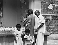 Sri Lankan family members offer gifts and prayers at a temple in Anuradhapura.