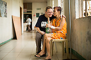 """Project HOPE volunteer Carma Erickson-Hurt visits with cancer patient Elenita Capulso, 84, in a hallway of Tapaz District Hospital on Panay Island, Philippines.  Erickson-Hurt has been visiting Capulso every day in the hospital. """"You are the first people who cared,"""" said Capulso."""