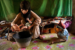 Asia, 14, washes her newborn at home while her 2-year-old daughter plays in Hajjah, Yemen, July 30, 2010. Asia is still bleeding and ill from childbirth, yet has no knowledge of how to care for herself nor access to maternal health care.