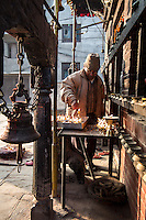 A Hindu priest lights candles at a shrine in Dhobi Chour.