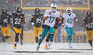 Dolphins quarterback Ryan Tannehill runs for a first down in the first quarter as the Pittsburgh Steelers host the Miami Dolphins at Heinz Field on Sunday, December 8, 2013.