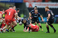 Eli Walker of the Ospreys © breaks away from the tackle from Morgan Allen of the Scarlets.  Guinness Pro12 rugby match, Ospreys v Scarlets at the Liberty Stadium in Swansea, South Wales on Saturday 26th March 2016.<br /> pic by  Andrew Orchard, Andrew Orchard sports photography.