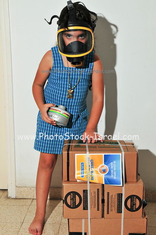 Gas Masks - All Israeli residents were issued gasmasks as a first means of defence against chemical or biological warfare. Young Girl of Seven tries on her gas mask. The sealed boxes contain the gas masks kits for the rest pf her family