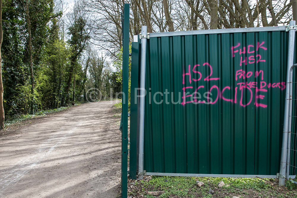Anti-HS2 graffiti on a security fence around an area alongside the Grand Union Canal cleared of trees and vegetation for the HS2 high-speed rail link is pictured on 6th April 2021 in Harefield, United Kingdom. Large swathes of the Colne Valley have been cleared of trees and vegetation for HS2 works which will include the construction of a Colne Valley Viaduct across lakes and waterways.