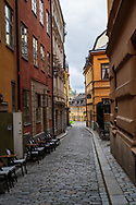 Stockholm, Sweden -- July 16, 2019. A morning vertical photo, shot down a winding side street in Stockholm.