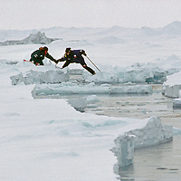 """Polar explorers work together to cross a """"lead"""" on the frozen Arctic Ocean."""
