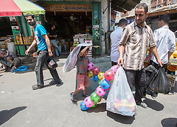 © Licensed to London News Pictures. 17/07/2014. Gaza.   A man and his son visit the Zawya market in Gaza on the tenth day of the war between Hamas and Israel as a 5 hour cease fire is agreed.   Photo credit : Alison Baskerville/LNP