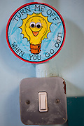 Sign to remind pupils and teachers to turn off the lights in their school to save energy.