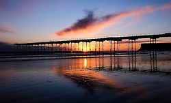 © Licensed to London News Pictures. <br /> 29/04/2016. <br /> Saltburn by the Sea, UK.  <br /> <br /> A cloud glows orange as it is lit by the light from the rising sun over the pier at Saltburn by the Sea. Further bad weather is expected to come down from the Arctic bringing snow and freezing temperatures to many northern and eastern parts of the country.<br />  <br /> Photo credit: Ian Forsyth/LNP