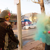 Keanu Mitchell, left, throws some powdered colors at  Tasha Nez, right, on the sidewalk outside of the Art123 Gallery during the Second Look on Second Street art walk in Gallup on Tuesday.