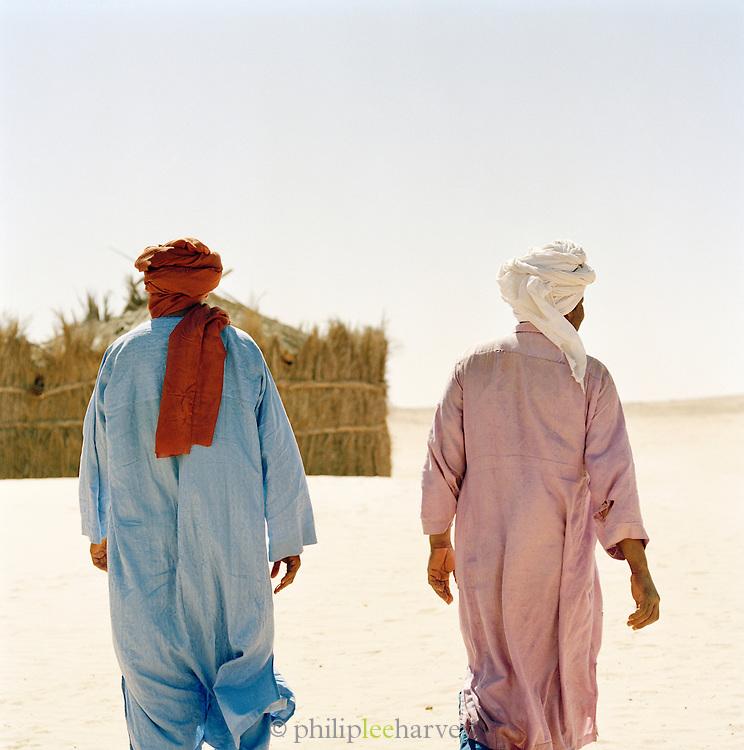Tuareg tribesmen walking in desert village, Libya