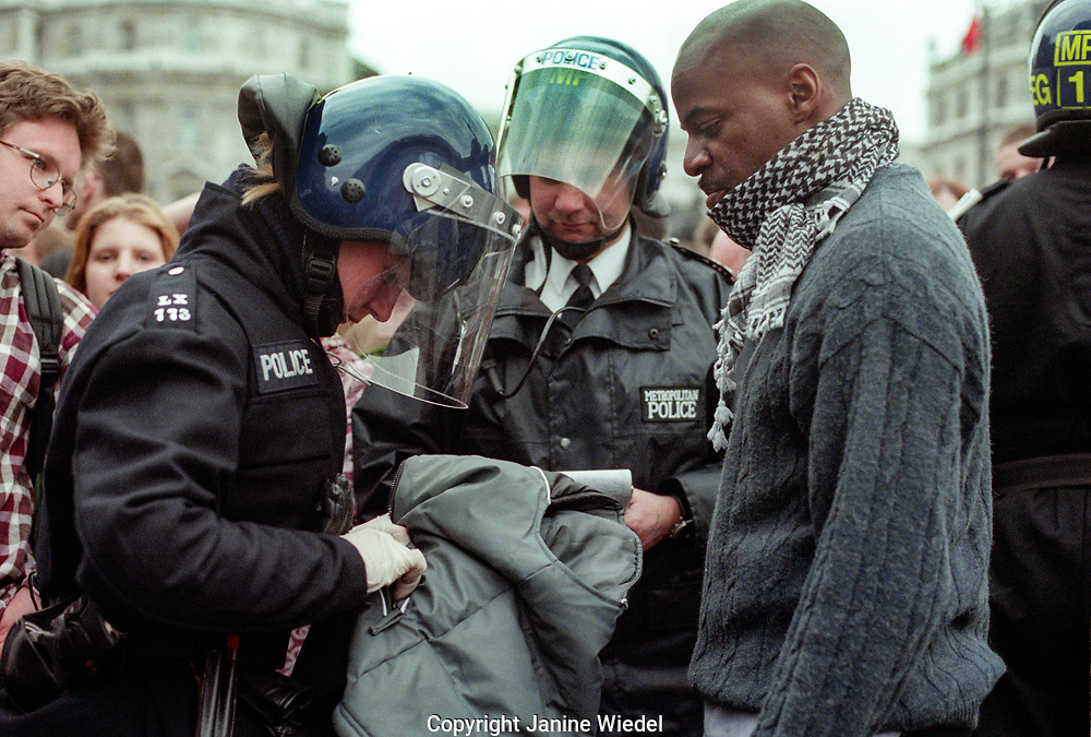 Black man being questioned by riot police during Mayday 2000 Mayday protest 2000