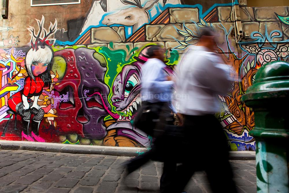 Men in business clothes walking down Hosier Lane, Melbourne Graffiti on Hosier Lane, Melbourne