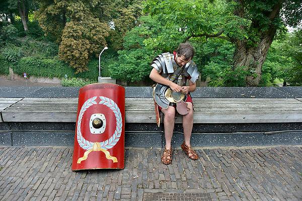Nederland,Nijmegen, 27-7-2014Een Romeinse soldaat maakt zich klaar om met drie burgers uit de Romeinse, antieke, tijd met twee ezels via het Trajanusplein richting museumpark Orientalis, mpo, in de Heilig Landstichting te lopen. Zij doen dit ter promotie van de activiteiten van dit museum over de wereldgodsdiensten wat voorheen het Bijbels openluchtmuseum heette.FOTO: FLIP FRANSSEN/ HOLLANDSE HOOGTE