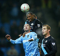 Photo. Aidan Ellis.<br /> Manchester City v Leicester City.<br /> FA Cup Rd3.<br /> 03/01/04.<br /> Leicester's Andy Impy beats Manchester's Antoine Sibierski to the ball