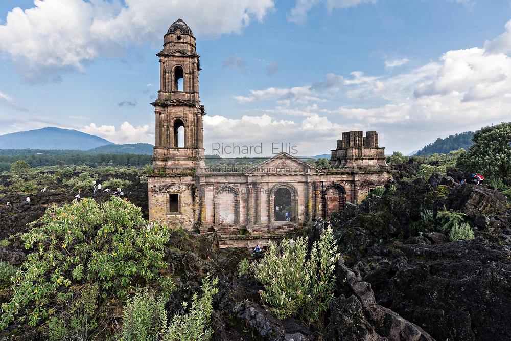 Tourists clammer around the steeple of San Juan Parangaricutiro church poking up out of a sea of dried lava rock in the remote village of San Juan Parangaricutiro, Michoacan, Mexico. This church is the only remaining structure left buried in the eight-year eruption of the Paricutin volcano which consumed two villages in 1943 and covered the region in lava and ash.