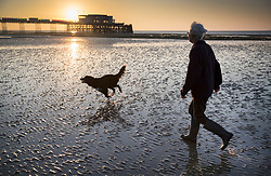 © Licensed to London News Pictures. 10/10/2018. Worthing, UK. A local resident walks her dog at sunrise in sight of Worthing Pier on a day when unseasonably high temperatures expected in parts of the UK. Photo credit: Peter Macdiarmid/LNP