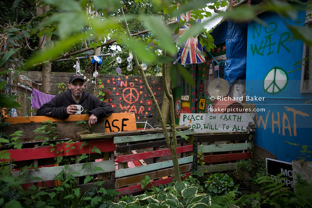 David Reynolds (aka Eco) is a long-term activist, campaigner in the peace movement and resident of the Faslane Peace Camp, Scotland. His home of three years is called the Earth Shack and is largely re-cycled from scrap and garbage found locally on rubbish tips. Eco leans against his garden fence holding a mug of coffee this chilly Sunday morning. Signs of his political beliefs adorn the place: CND logos and Peace on Earth statements. His mother was a ?Carnie? (after the word Carnival, someone working on the fairgrounds) so perhaps it?s from her that he more enjoys an alternative outdoor camping lifestyle after a few years in the army. Faslane Peace Camp is a makeshift site alongside Faslane Naval base where Trident nuclear deterrent missiles and submarines dock. The camp has been occupied continuously, in a few different locations, since 1982.