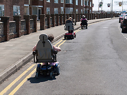 Wheelchair users riding down the road after not being able to get up high kerb onto the pavement.