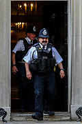 Two police officers are seen leaving UK Prime Minister's Office in Downing Street, as the row over Prime Minister Boris Johnson's top aide Dominic Cummings' Durham trip, continues on Wednesday, May 27, 2020. The prime minister's populist appeal has been hammered by the news that, as the coronavirus outbreak raged, chief adviser Cummings drove 250 miles (400 kilometres) to his parents' house while he was falling ill with suspected COVID-19 allegedly flouting lockdown rules that the government had imposed on the rest of the country. (Photo/ Vudi Xhymshiti)