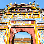 A brightly painted gate at the Imperial City in Hue, Vietnam. A self-enclosed and fortified palace, the complex includes the Purple Forbidden City, which was the inner sanctum of the imperial household, as well as temples, courtyards, gardens, and other buildings. Much of the Imperial City was damaged or destroyed during the Vietnam War. It is now designated as a UNESCO World Heritage site. This gate was an entrance to the Dien Tho Residence. Constructed in 1804, this compound was was the Queen Mother's or Emperor's Grandmother's living quarters.