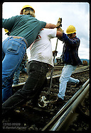 Track gang takes Iwo Jima stance as they wrestle jack bar to fix switch track;UPRR yard, Portland Oregon