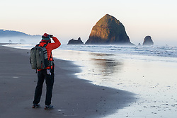 Photographer and Haystack Rock on Cannon Beach. Ecola State Park, Oregon, USA.