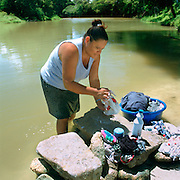 Mestizo female washing clothes beside Macal river