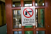 A Gun free zone sign on the entrance door of the Lavender Hill township Community Centre in the Cape Town region of South Africa.