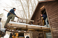 Martin Carney slides ice blocks to Ian Adams as they load the 9th out of 10 rows to fill the Rockywald Ice House on Thursday afternoon.  (Karen Bobotas/for the Laconia Daily Sun)