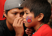 UA student in pre-health, Leland Gray, 18, (left), of Mexican Water, Arizona, paints Wildcat mascot symbols on the face of Taja June, 10, while attending the NASA Wildcat Family Pride Weekend at the University of Arizona, Tucson, Arizona, USA.