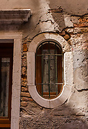 An unusual oval-shaped window, seen on a narrow street of Venice, Italy