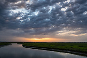 Sunrise over the tidal salt marshes of the Cape Romain National Wildlife Refuge at sunrise near Charleston, South Carolina. The 66,287 acre National Wildlife Refuge encompass water impoundments, creeks, bays, emergent salt marsh and barrier islands most of which is only accessible by boat.