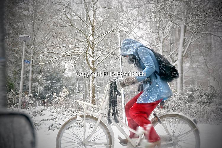 Nederland, Nijmegen, 11-12-2017 Een flinke sneeuwbui gaat over de stad. Hier trotseert een fietser het weer.Foto: Flip Franssen