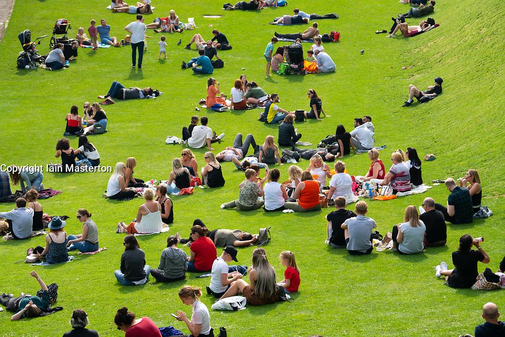 People sitting on lawn at Princes Street Gardens in warm summer weather in Edinburgh, Scotland UK