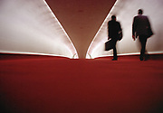 Businessmen walking through a passageway in the TWA Terminal, designed by Eero Saarinen, now it is a hotel