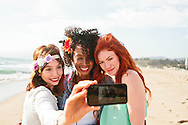 """Three young women taking a """"selfie"""" photo at the beach."""