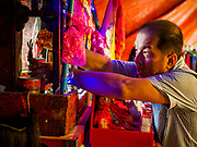 """26 FEBRUARY 2018 - BANGKOK, THAILAND: The manager of an opera troupe makes an offering at the troupe's shrine before a Chinese Opera at the Phek Leng Shrine in the Khlong Toey section of Bangkok. The shrine traditionally hosts a Chinese Opera just after the end of Lunar New Year festivities. Thailand is home to the largest population of overseas Chinese in the world, and Chinese cultural practices, like Chinese opera, called """"ngiew"""" in Thailand, are popular. Many of the performers are ethnic Thais who don't speak Chinese. They learn their lines phonetically.   PHOTO BY JACK KURTZ"""