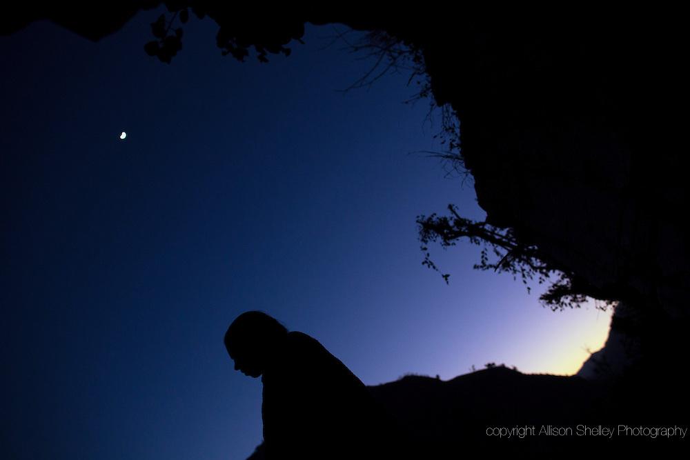 The moon glows overhead as Maisara, 15, prepares to sleep under a rock outcropping in observance of chaupadi in Kalekanda village, Achham, Nepal.