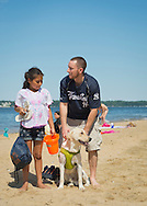 Sands Point, New York, U.S. - July 5, 2014 - Jordan, a yellow labrador, and his family visit the sandy shoreline at Sands Point Preserve on the North Shore Gold Coast along Long Island Sound, during Independence Day weekend. The public beach had many visitors this Saturday of the long holiday weekend when sunny warm weather arrived after the rainy July 4th.