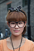 Model with no lenses in her glasses (this is a very common fashion statement in Beijing) being photographed front and back for a clothing website on Yandaixiejie Street (meaning Tobacco Pipe Lane) in Beijing, China. Located near to Houhai in downtown Beijing, Yandai Xiejie Street is a Hutong which attracts many tourists at day and night to it's souvenir shops and towards the bar area it leads to.