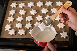 Close-up of a woman icing star shape cinnamon with basting brush, Munich, Bavaria, Germany