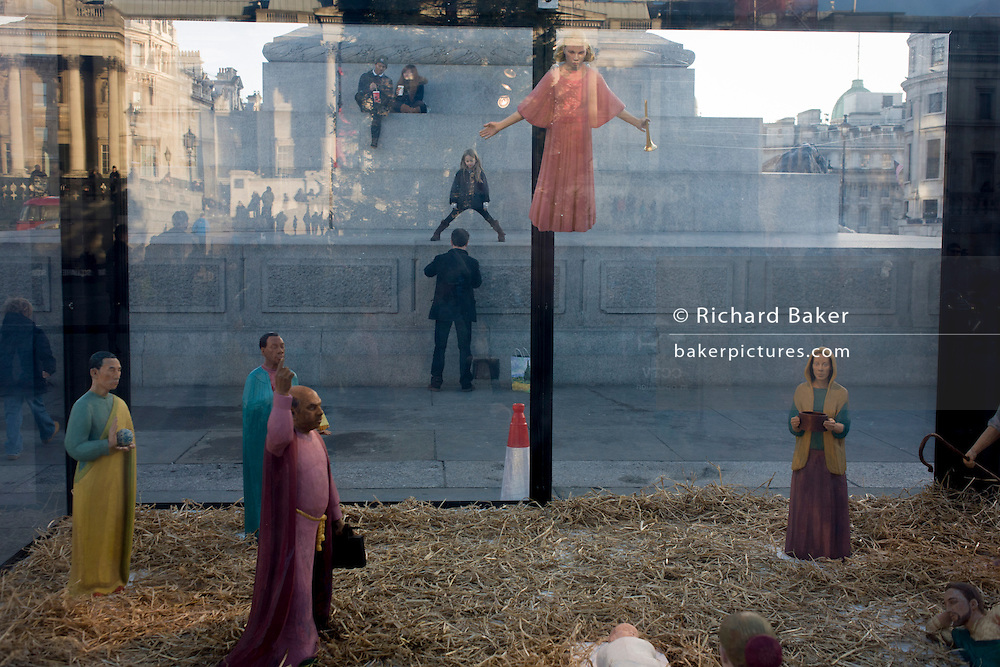 A holy nativity scene titled Christmas Crib by the artist Tomoaki Suzuki with background tourists in London's Trafalgar Square. Juxtaposed under the Angel Gabriel are a man's legs who is actually hauling himself up on to a plinth of Nelson's comumn. Encased within a transparent perspex box are the pilgrims who are apparently paying their respects to the infant Jesus in that famous Christian religious event. The new crib was commissioned in 2006 by St Martin-in-the-Fields providing a significant new public art work embodies characters representing different ethnicities - Middle eastern, Caucasian, African and Asian. The 11 painted lime wood carving are 40% life-size and were a collaboration with fashion designer Jessica Ogden who created timeless silk costumes for each of the characters.