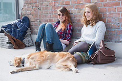 Two friends with dog in front of brick wall, Munich, Bavaria, Germany