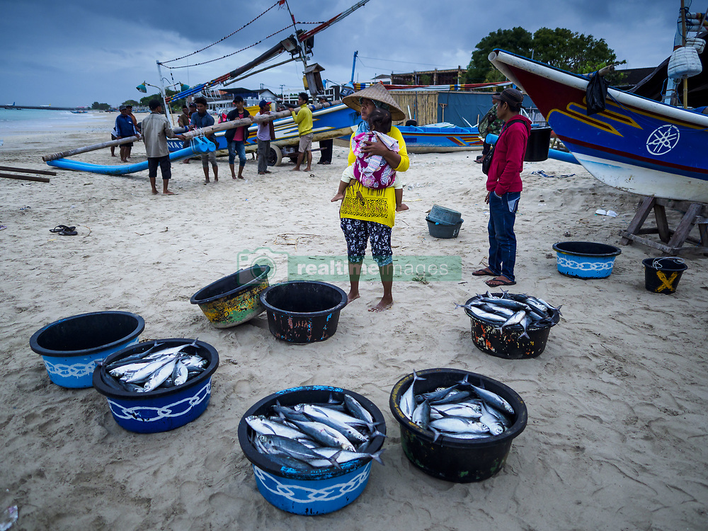August 3, 2017 - Kuta, Bali, Indonesia - A woman sells fish caught overnight by villagers who live along Jimbrana Beach in Kuta. The beach is close to the airport and a short drive from other beaches in southeast Bali. Jimbrana was originally a fishing village with a busy local market. About 25 years ago, developers started building restaurants and hotels along the beach and land prices are rising. The new emphasis on tourism is changing the nature of the area but the fishermen are still busy very early in the morning. (Credit Image: © Jack Kurtz via ZUMA Wire)