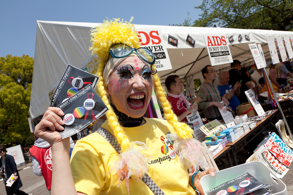 A man in drag handing out AIDS awareness packs at Tokyo Rainbow Pride festival, Yoyogi Park, Tokyo, Japan. Sunday April 27th 2014 This was the third year this annual gay-pride event has been held in Japan capital.with food, fashion and health care stalls and musical performances set up in Yoyogi Park event square and a colourful parade around Shibuya at 1pm.
