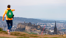 Edinburgh, Scotland, UK. 5 April, 2020. On the second Sunday of the coronavirus lockdown in the UK the public are outside taking their daily exercise. A woman walking on Salisbury Crags in Holyrood Park points towards Edinburgh Castle in distance. Iain Masterton/Alamy Live News