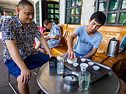 """14 FEBRUARY 2019 - SIHANOUKVILLE, CAMBODIA:  Men who work for Chinese enterprises in Sihanoukville drink tea in front of their apartment building. There are thousands of Chinese workers in Sihanoukville who work to support the casino and hotel industry in the town. There are about 80 Chinese casinos and resort hotels open in Sihanoukville and dozens more under construction. The casinos are changing the city, once a sleepy port on Southeast Asia's """"backpacker trail"""" into a booming city. The change is coming with a cost though. Many Cambodian residents of Sihanoukville  have lost their homes to make way for the casinos and the jobs are going to Chinese workers, brought in to build casinos and work in the casinos.      PHOTO BY JACK KURTZ"""