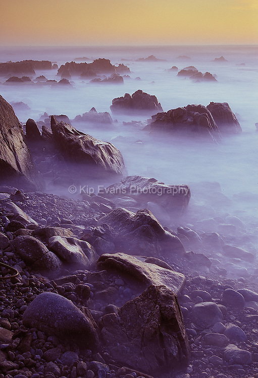Fog hugs the rocky shoreline along Pebble Beach, California.